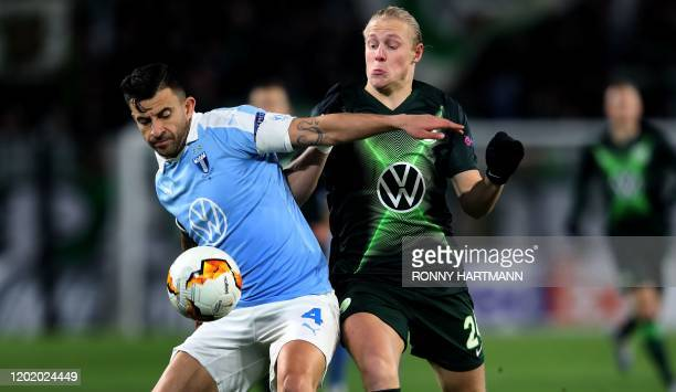 Malmo's Swedish defender Behrang Safari and Wolfsburg's Austrian midfielder Xaver Schlager vie for the ball during the Europa League last 32 first...