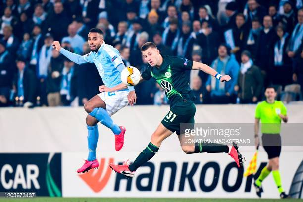 Malmo's Swedish forward Isaac Kiese Thelin vies with Wolfsburg's German defender Robin Knoche during the Europa League Last 32 Second Leg football...