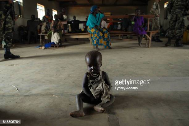 A malnourished baby sits near a Pakistani Peacekeeper as thousands of people displaced from dozens of surrounding villages due to recent fighting...