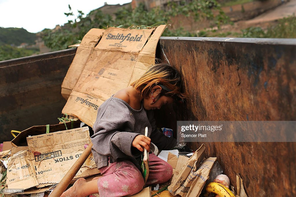 A malnourished girl plays in a dumpster in a gang infested neighborhood on July 17, 2012 in Tegucigalpa, Honduras. Honduras now has the highest per capita murder rate in the world and its capital city, Tegucigalpa, is plagued by violence, poverty, homelessness and sexual assaults. With an estimated 80% of the cocaine entering the United States now being trans-shipped through Honduras, the violence on the streets is a spillover from the ramped rise in narco-trafficking. The non-governmental organization Doctors Without Borders has set up a program in the capital that looks to provide medical and psychological care to the homeless population. Each day a team goes out into the streets to meet with vulnerable groups of homeless to assess their needs.