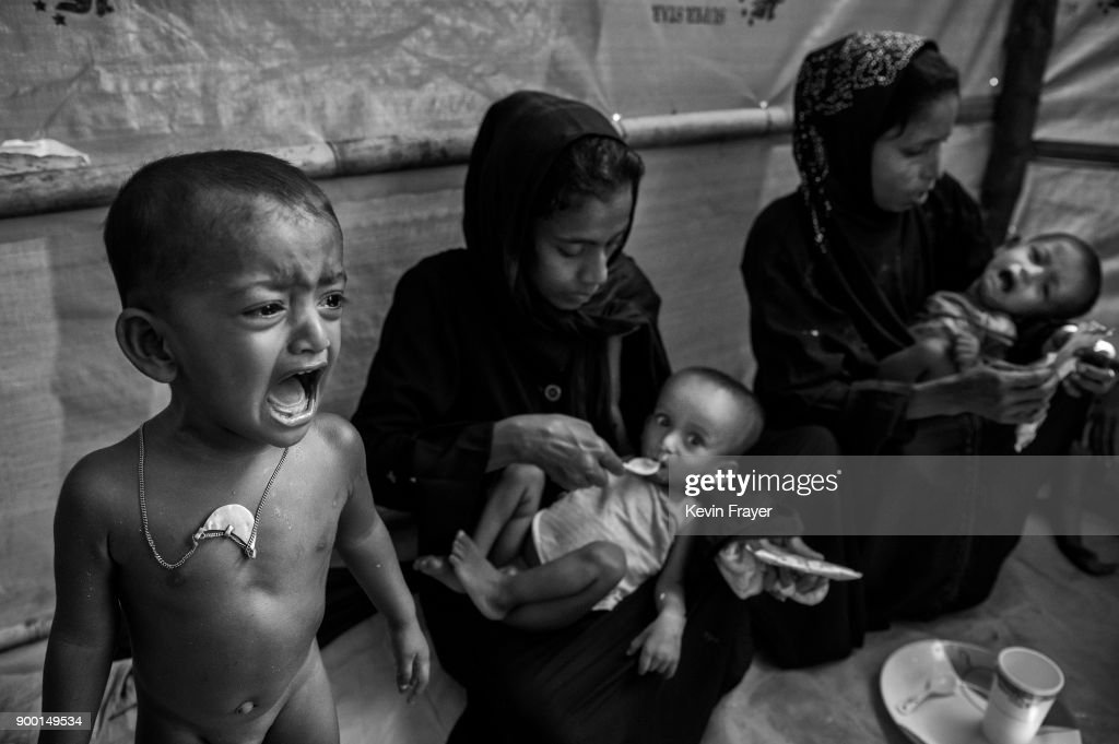 "COX'S BAZAR, BANGLADESH - OCTOBER 25: A malnourished Rohingya Muslim refugee boy cries as mothers feed high calorie peanut paste to their malnourished children at a field clinic by the NGO Action Against Hunger (ACF) on October 25, 2017 at the Kutapalong refugee camp in Cox's Bazar, Bangladesh. More than 600,000 Rohingya refugees have flooded into Bangladesh to flee an offensive by Myanmar's military that the United Nations has called ""a textbook example of ethnic cleansing"". The refugee population continues to swell further, with thousands more Rohingya Muslims making the perilous journey on foot toward the border, or paying smugglers to take them across by water in wooden boats. Hundreds are known to have died trying to escape, and survivors arrive with horrifying accounts of villages burned, women raped, and scores killed in the ""clearance operations"" by Myanmar's army and Buddhist mobs that were sparked by militant attacks on security posts in Rakhine state on August 25, 2017. What the Rohingya refugees flee to is a different kind of suffering in sprawling makeshift camps rife with fears of malnutrition, cholera, and other diseases. Aid organizations are struggling to keep pace with the scale of need and the staggering number of them — an estimated 60 percent — who are children arriving alone. Bangladesh, whose acceptance of the refugees has been praised by humanitarian officials for saving lives, has urged the creation of an internationally-recognized ""safe zone"" where refugees can return, though Rohingya Muslims have long been persecuted in predominantly Buddhist Myanmar. World leaders are still debating how to confront the country and its de facto leader, Aung San Suu Kyi, a Nobel Peace Prize laureate who championed democracy, but now appears unable or unwilling to stop the army's brutal crackdown."