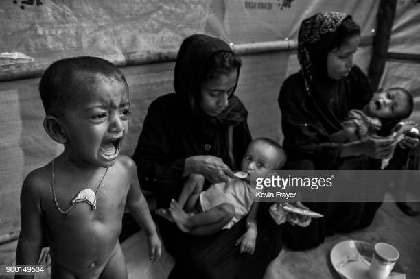 COX'S BAZAR BANGLADESH OCTOBER 25 A malnourished Rohingya Muslim refugee boy cries as mothers feed high calorie peanut paste to their malnourished...