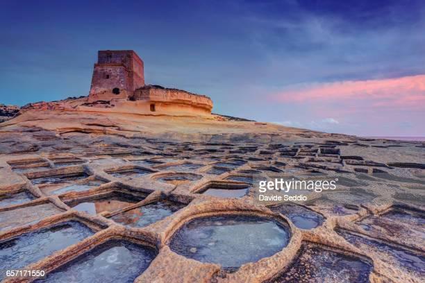 Malta, Gozo Island, Xlendi, watchtower and salt pans at sunset
