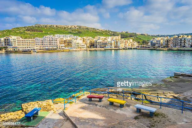 Malta, Gozo, Marsalforn, View of town harbor with waterfront buildings from seaside terrace