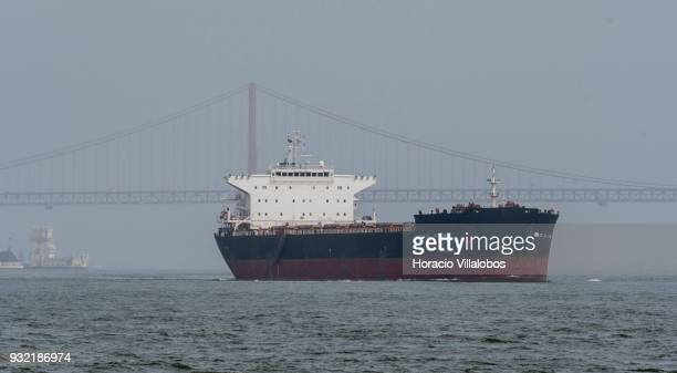 Malta registered Bulk Carrier 'Iolcos Vision' leaves behind 25 de Abril bridge and Belem Tower as she sails off harbor on March 13 2018 in Lisbon...