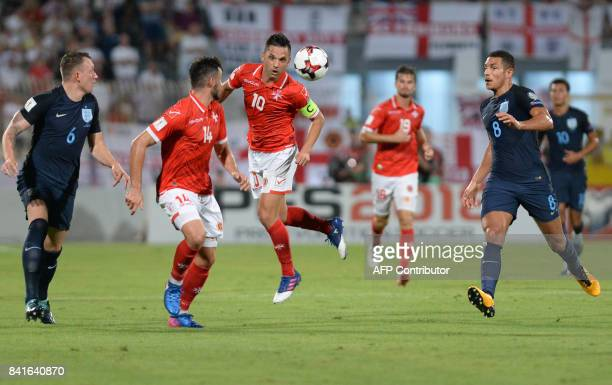 Malta's Andre Schembri heads the ball towards teammate Jean-Paul Farrugia as England's Phil Jones and Jake Livermore look on during the FIFA 2018...