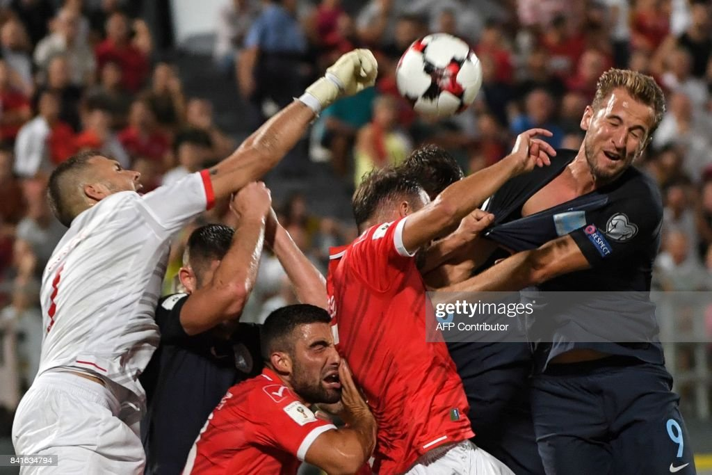 Malta's goalkeeper Andrew Hogg (L) jumps to save the ball during the 2018 FIFA World Cup qualifying football match Malta vs England at the National Stadium in Malta's Ta' Qali village, on September 1, 2017. /