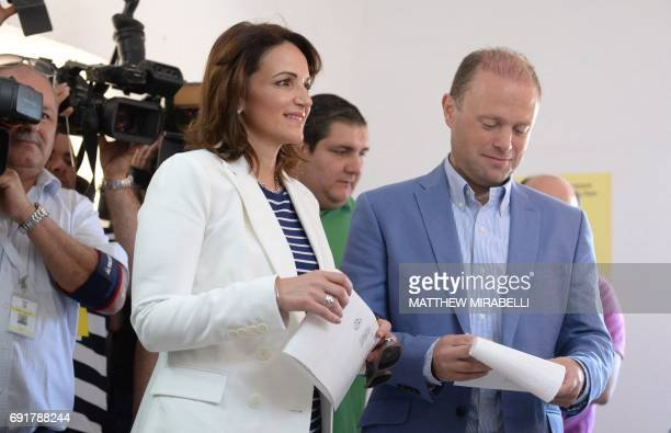 Malta's Prime Minister Joseph Muscat and his wife Michelle Muscat prepare to vote at a polling station in his home town of Burmarrad on June 3 2017...