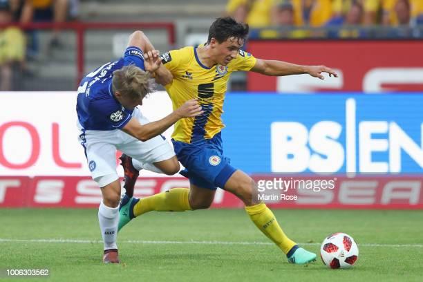 Malte Amundsen of Braunschweig is challenged by Marco Thiede of Karlsruhe during the 3 Liga match between Eintracht Braunschweig and Karlsruher SC at...