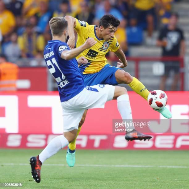 Malte Amundsen of Braunschweig shoots the ball under pressure from Marco Thiede of Karlsruhe during the 3 Liga match between Eintracht Braunschweig...