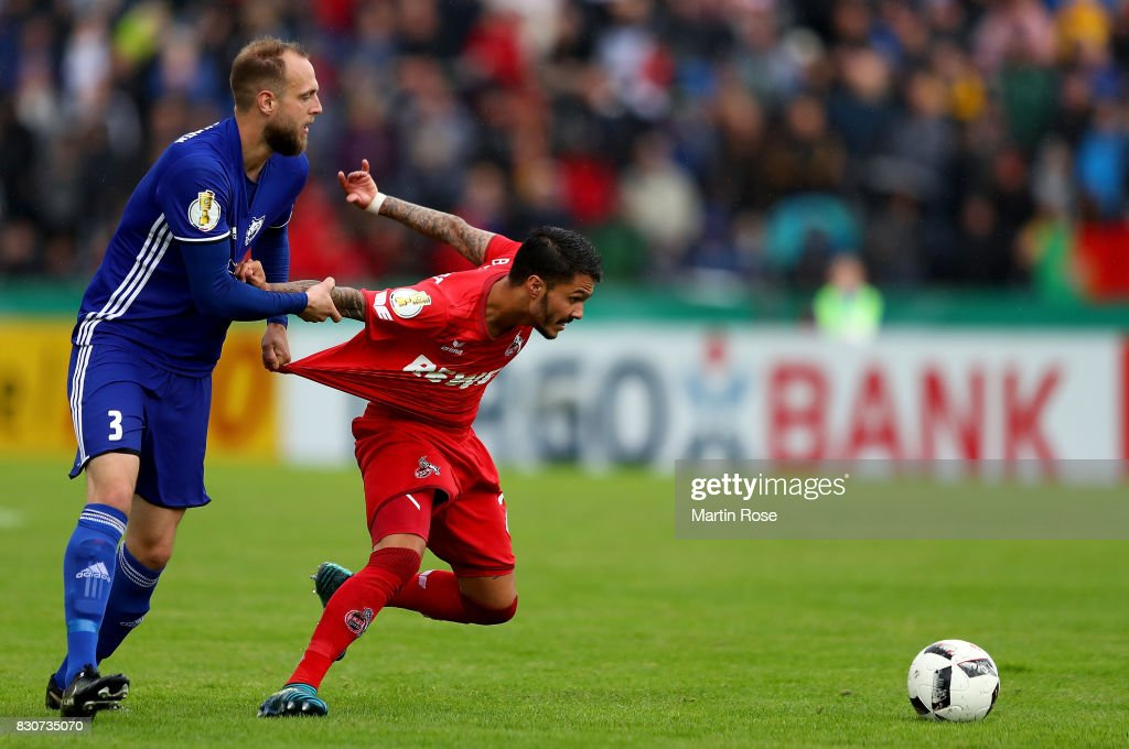 Malte Soentgerath (L) of Leher TS and Leonardo Bittencourt of Koeln battle for the ball during the DFB Cup first round match between Leher TS and 1. FC Koeln at Nordseestadion on August 12, 2017 in Bremerhaven, Germany.