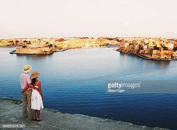 maltese islands, malta, valletta, couple by sea looking at city - マルタ島 ストックフォトと画像