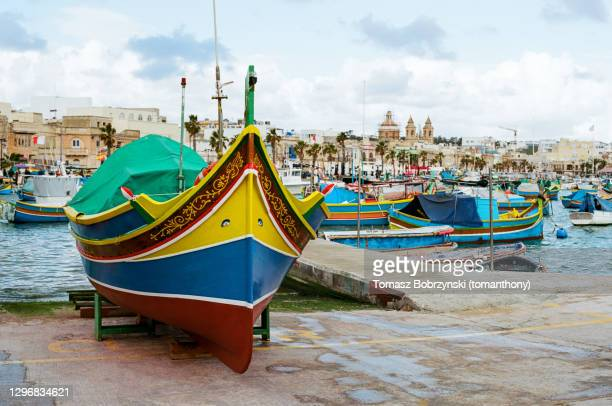 maltese luzzu fishing boats in the harbour of marsaxlokk - marsaxlokk stock pictures, royalty-free photos & images