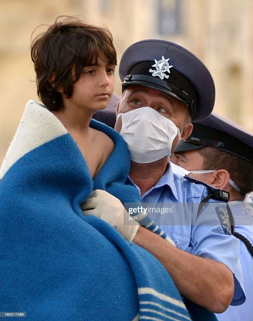 A Maltese policeman carries a child rescued by the Armed forces of Malta at Hay Wharf in Valletta on October 12, 2013. More than 140 survivors, plucked from the sea after their overloaded boat sank in the latest deadly migrant tragedy to hit the Mediterranean, arrived in Malta. The sinking killed more than 30, most of them women and children, when the boat packed with people desperate to reach European shores went down off Malta near the Italian island of Lampedusa, according to officials.