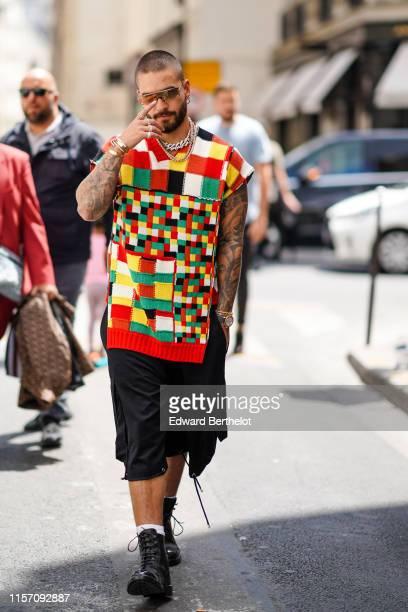 Maluma wears a multicolor checked wool sleeveless pullover, black shorts, sunglasses, outside JW Anderson, during Paris Fashion Week - Menswear...