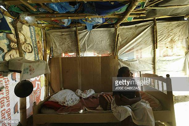 Malvina Alfaro resident of La Esperanza community in Soyapango San Salvador remains 04 January 2008 inside her shack seeking shelter from the strong...