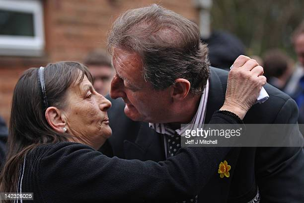 Malvina Wilson the widow of Jocky Wilson hugs Eric Bristow as family and friends gather for the funeral of Jocky at Kirkcaldy crematorium on April 2...