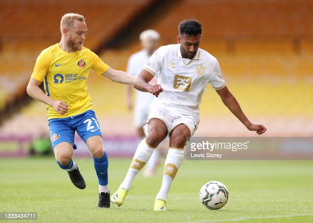 Malvind Benning of Port Vale battles for possession with Alex Pritchard of Sunderland during the Carabao Cup First Round match between Port Vale and...