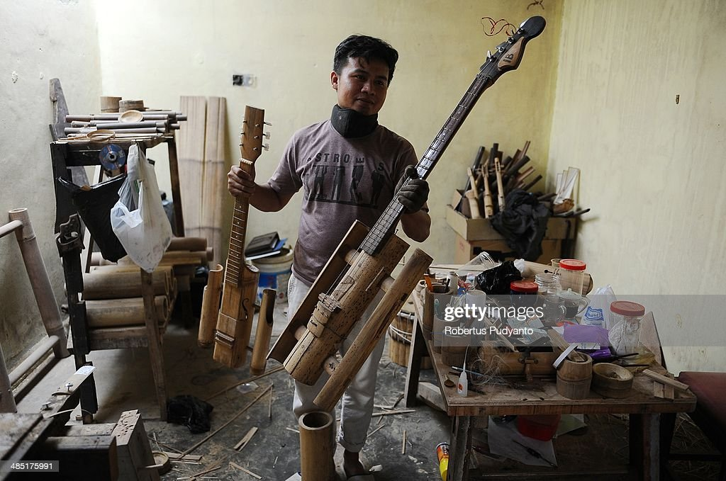 Malvino Purba Alam, 32, Head of Research Department Indonesian Bamboo Community carries a bamboo guitar and a bamboo violin at his workshop on April 17, 2014 in Bandung, Java, Indonesia. Adang Muhidin, founder of Indonesian Bamboo Community, and his friends make sustainable bamboo musical instruments (guitar, violin, bass, trumpet, clarinet, saxophone, drums) a nod to the rise of the creative economy in Indonesia.