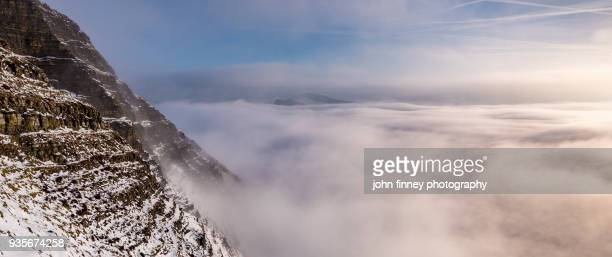 Mam Tor cliffs with fog and snow at sunrise in the English Peak District. UK.