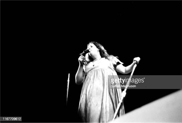 Mama Cass Elliot seen from the press pit in her long satin dress mike in right hand mike stand in her left hand performing with the band The Mamas...