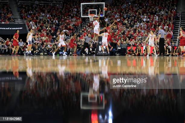 Mamadi Diakite of the Virginia Cavaliers blocks the shot of Dwayne Sutton of the Louisville Cardinals during the second half at KFC YUM Center on...