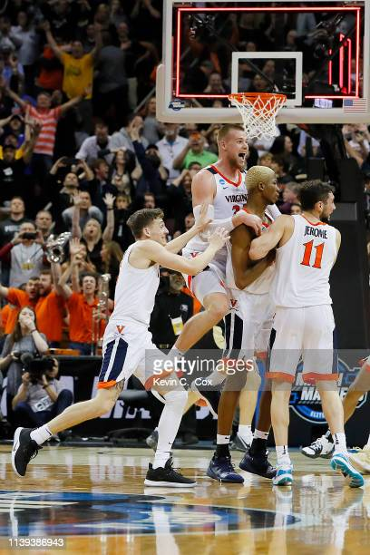 Mamadi Diakite of the Virginia Cavaliers celebrates with teammates after making a game-tying shot over Matt Haarms of the Purdue Boilermakers to...