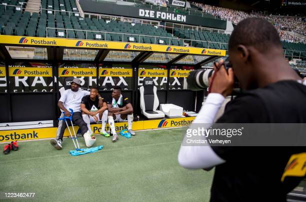 Mamadou Doucoure of Borussia Moenchengladbach take pictures of Marcus Thuram Alassane Plea and Breel Embolo after the Bundesliga match between...