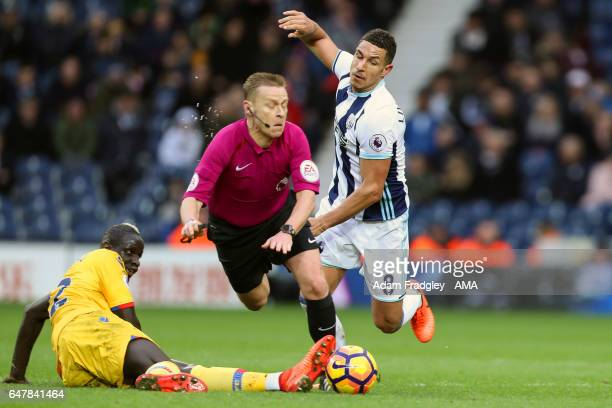 Mamadou Sakho of Crystal Palace and Jake Livermore of West Bromwich Albion combine to collide with the referee Mike Jones as they challenge for the...
