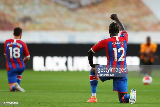Mamadou Sakho of Crystal Palace takes a knee in support of the Black Lives Matter movement during the Premier League match between Wolverhampton...