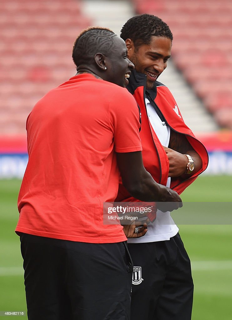 Mamadou Sakho of Liverpool (L) dresses ex-Liverpool player Glen Johnson of Stoke City in a Liverpool tracksuit top prior to the Barclays Premier League match between Stoke City and Liverpool at Brittania Stadium on August 9, 2015 in Stoke on Trent, England.
