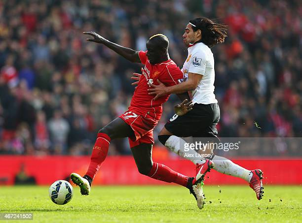 Mamadou Sakho of Liverpool is challenged by Radamel Falcao of Manchester United during the Barclays Premier League match between Liverpool and...