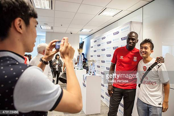 Mamady Sidibe former Stoke player takes a photo with a fan during a QA at the Barclays office during the Barclays Asia Trophy 2015 Ticket Launch day...