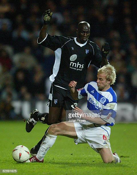 Mamady Sidibe of Gillingham is tackled by Andrew Davies of QPR during the CocaCola Championship match between Queens Park Rangers and Gillingham at...