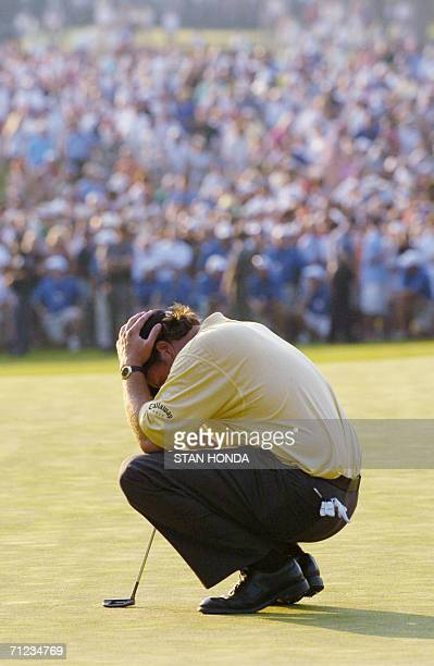 Mamaroneck, UNITED STATES: Phil Mickelson of the US holds his head while waiting for Kenneth Ferrie to putt on the 18th green during the final round...