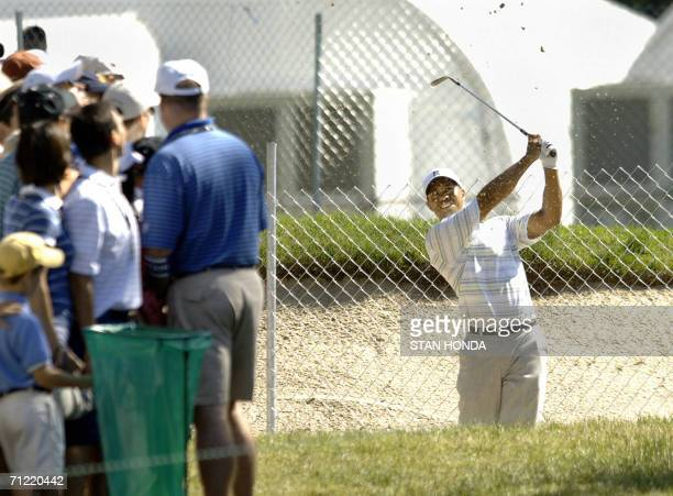 Mamaroneck, UNITED STATES: Tiger Woods of the US hits to the 16th green from a sand trap on an adjacent course during the second round of the US Open...