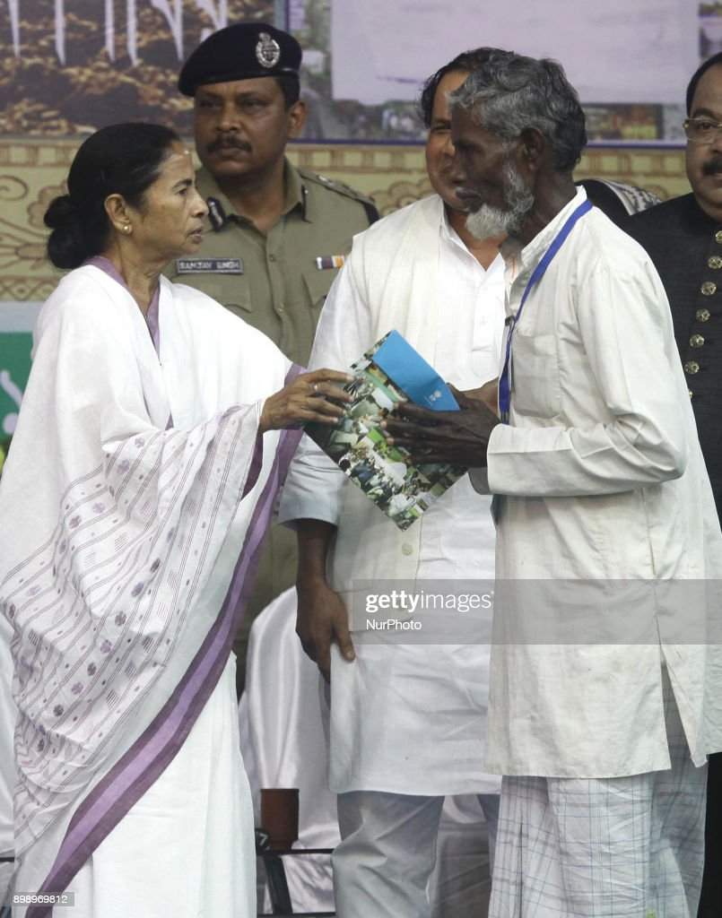 Mamata Banerjee Chief Minister of West Bengal provides with financial assistance to village old Man for the loss of his crops in the floods during a programme at Sagar Islan on December 27,2017 in India.