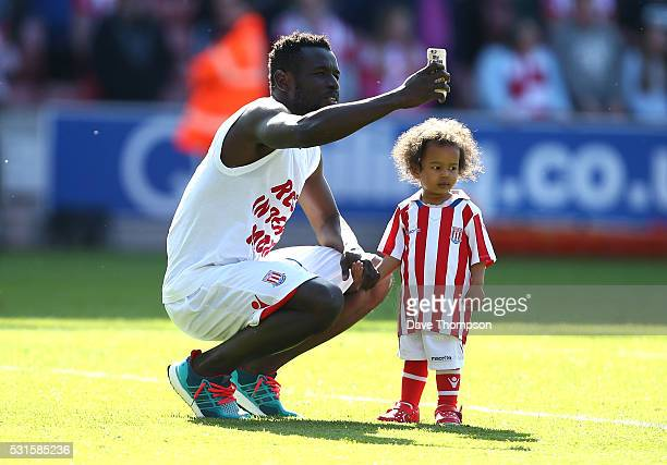 Mame Biram Diouf of Stoke City and his child are seen after the Barclays Premier League match between Stoke City and West Ham United at the Britannia...