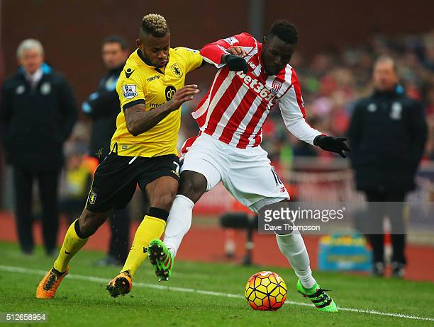 Mame Biram Diouf of Stoke City and Leandro Bacuna of Aston Villa compete for the ball during the Barclays Premier League match between Stoke City and...