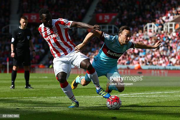 Mame Biram Diouf of Stoke City and Mark Noble of West Ham United compete for the ball during the Barclays Premier League match between Stoke City and...