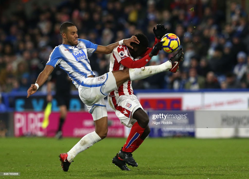 Mame Biram Diouf of Stoke City and Mathias Jorgensen of Huddersfield Town battle for possesion and Mame Biram Diouf of Stoke City handles the ball which leads to a yellow card during the Premier League match between Huddersfield Town and Stoke City at John Smith's Stadium on December 26, 2017 in Huddersfield, England.