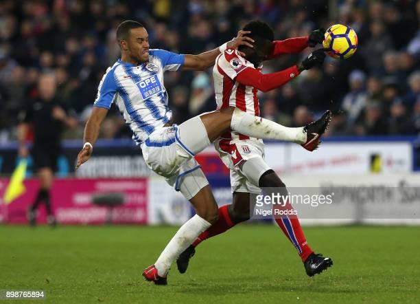 Mame Biram Diouf of Stoke City and Mathias Jorgensen of Huddersfield Town battle for possesion and Mame Biram Diouf of Stoke City handles the ball...