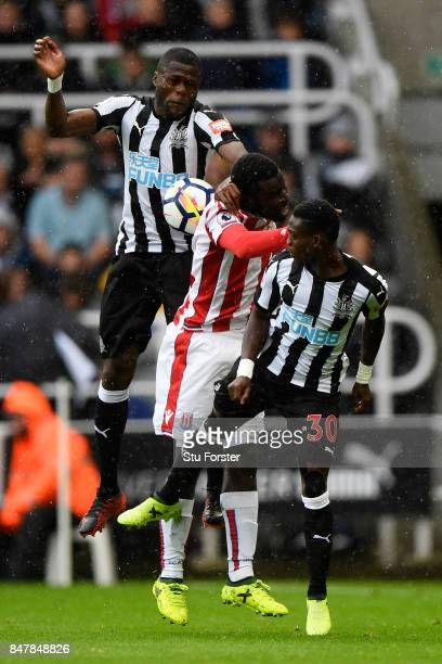 Mame Biram Diouf of Stoke City attempts to win a header while under pressure from Christian Atsu of Newcastle United and Chancel Mbemba of Newcastle...