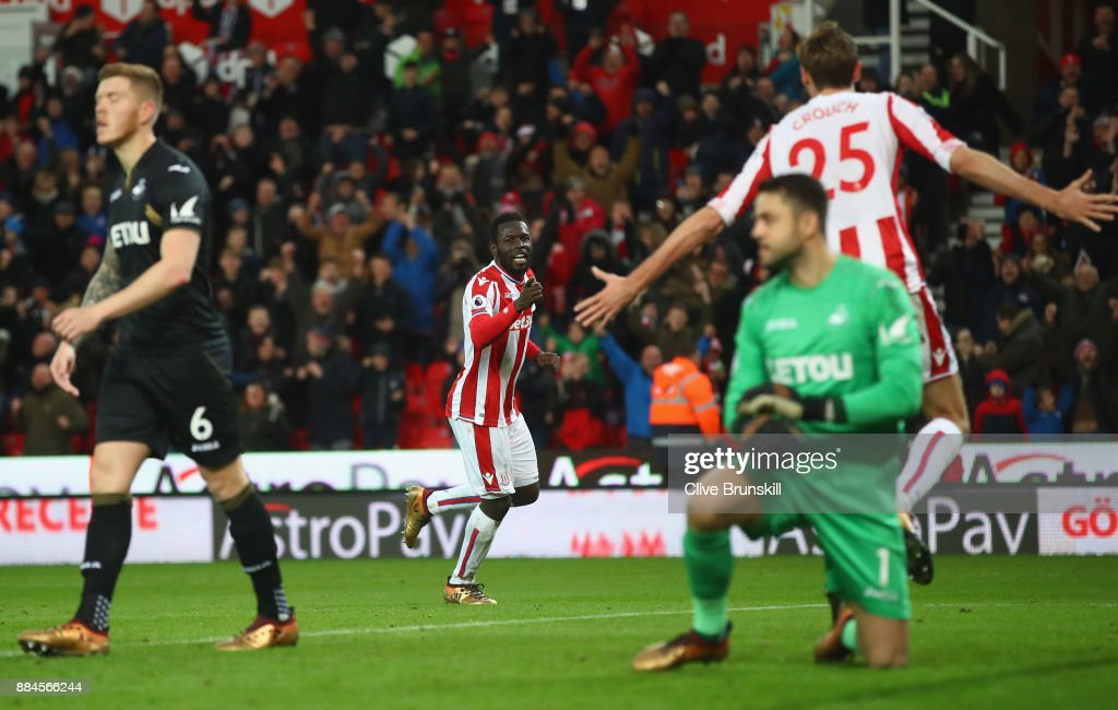 Mame Biram Diouf of Stoke City celebrates after scoring his sides second goal with Peter Crouch of Stoke City during the Premier League match between Stoke City and Swansea City at Bet365 Stadium on December 2, 2017 in Stoke on Trent, England.