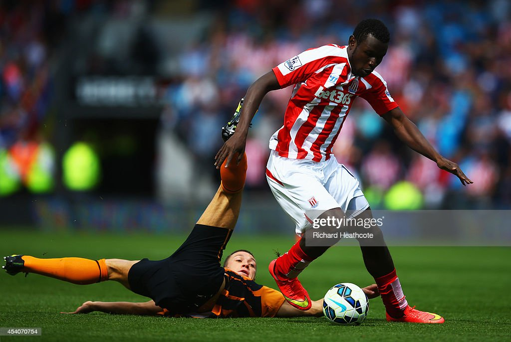 Mame Biram Diouf of Stoke City evades James Chester of Hull City during the Barclays Premier League match between Hull City and Stoke City at KC Stadium on August 24, 2014 in Hull, England.