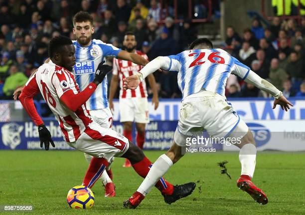 Mame Biram Diouf of Stoke City is tackled by Christopher Schindler of Huddersfield Town in the penalty area but no penalty is awarded during the...