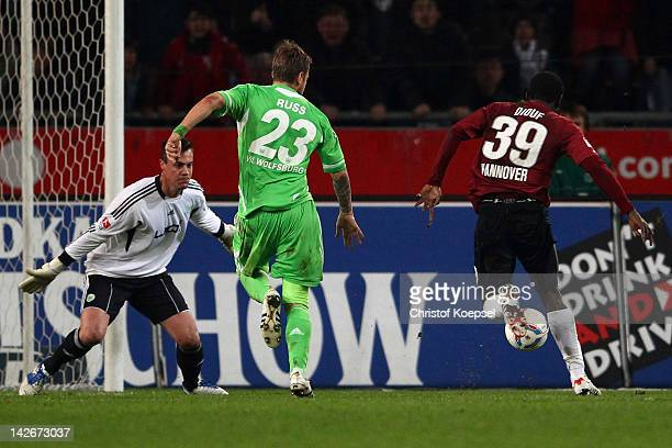Mame Diouf of Hannover scores the first goal against Diego Benaglio and Marco Russ of Wolfsburg during the Bundesliga match between Hanover 96 and...