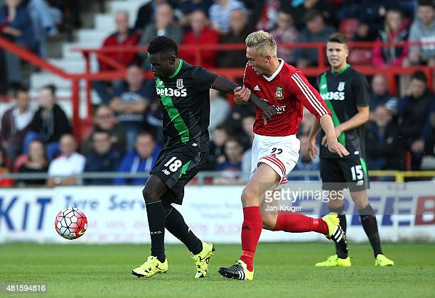 Mame Diouf of Stoke City holds off Jon Royle of Wrexham during the pre season friendly match between Wrexham and Stoke City at Racecourse Ground on...