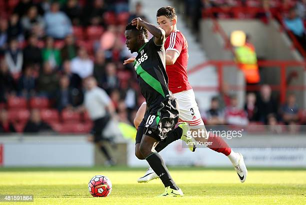 Mame Diouf of Stoke City holds off Sean Newton of Wrexham for his goal during the pre season friendly match between Wrexham and Stoke City at...