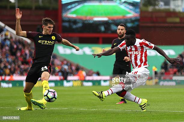Mame Diouf of Stoke City shoots at goal under pressure from John Stones of Manchester City during the Premier League match between Stoke City and...
